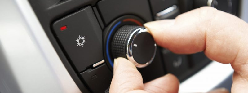Close Up Of Hand Adjusting Car Air Conditioning Control On Dashboard